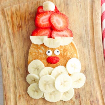 santa pancakes - christmas and holiday breakfast - made with bananas for a beard, strawberries for a hat, and candy eyes on top of a homemade pancake