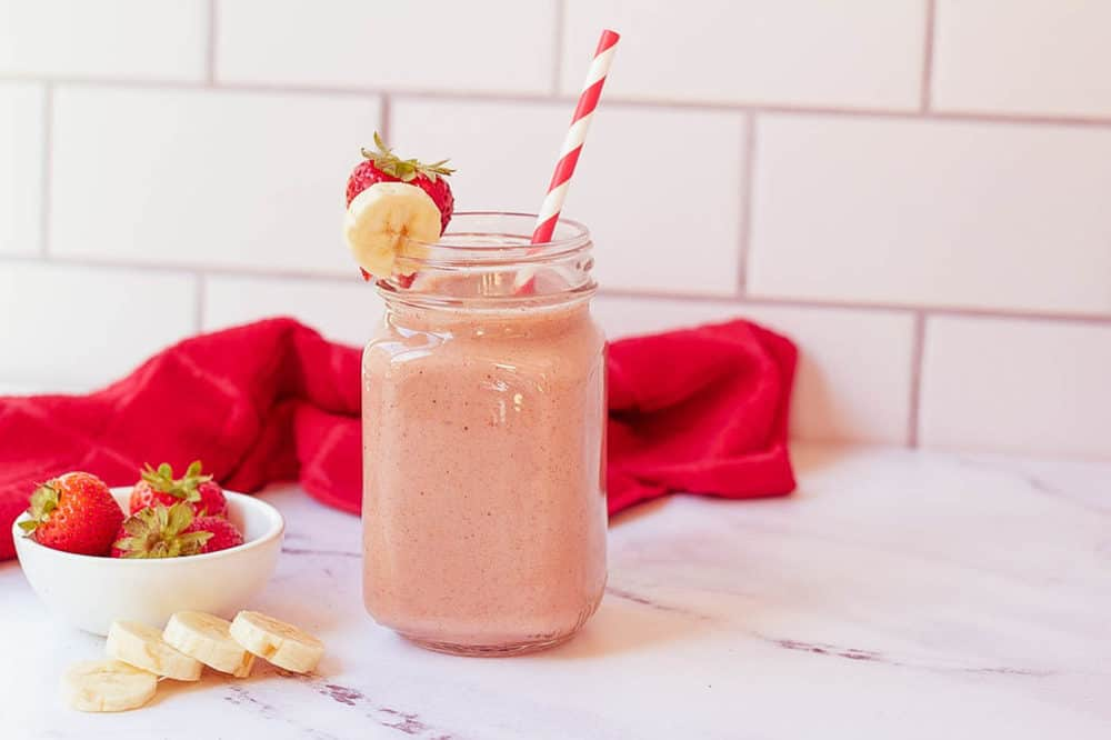 strawberry and banana smoothie in a glass mason jar with a straw