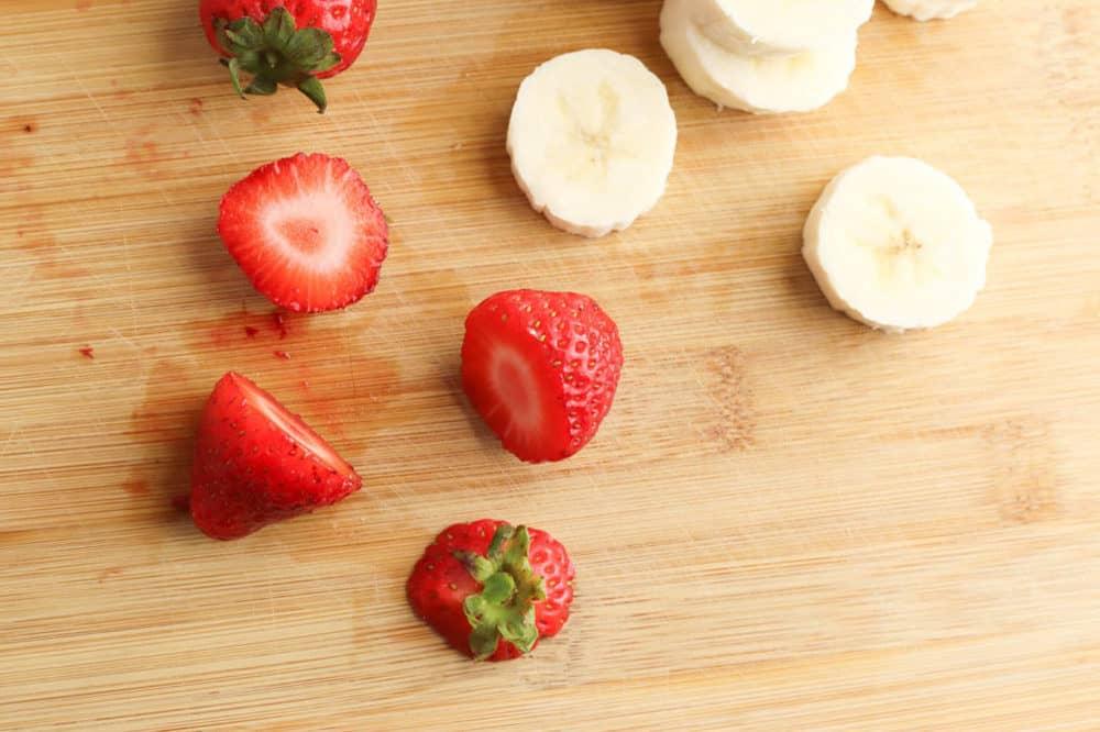 cut strawberries and banana on a cutting board