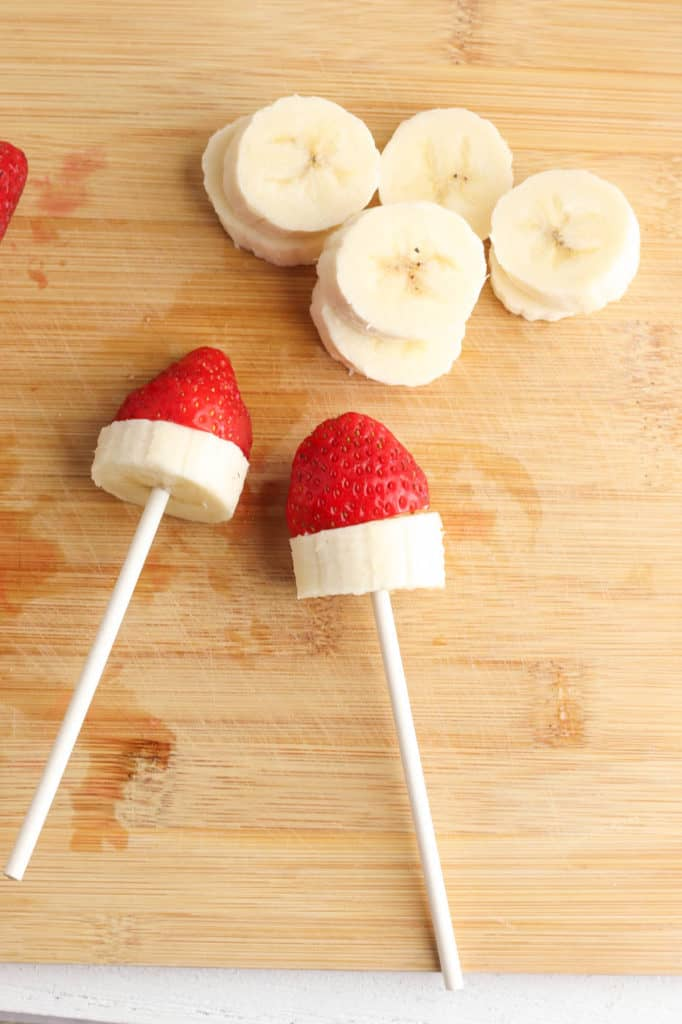 strawberries and bananas being assembled on skewers