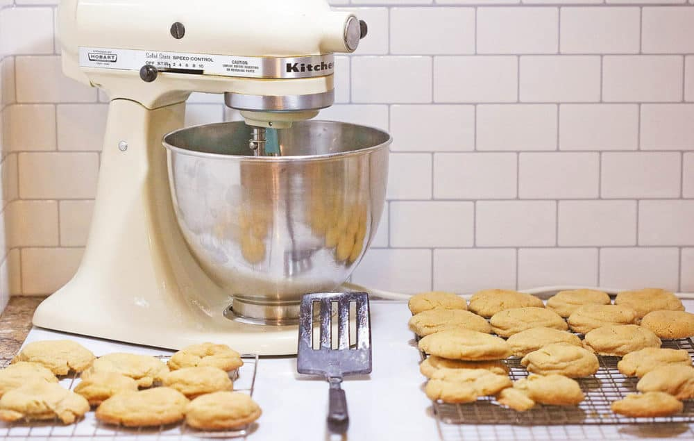 cookies on a baking sheet next to an electric mixer