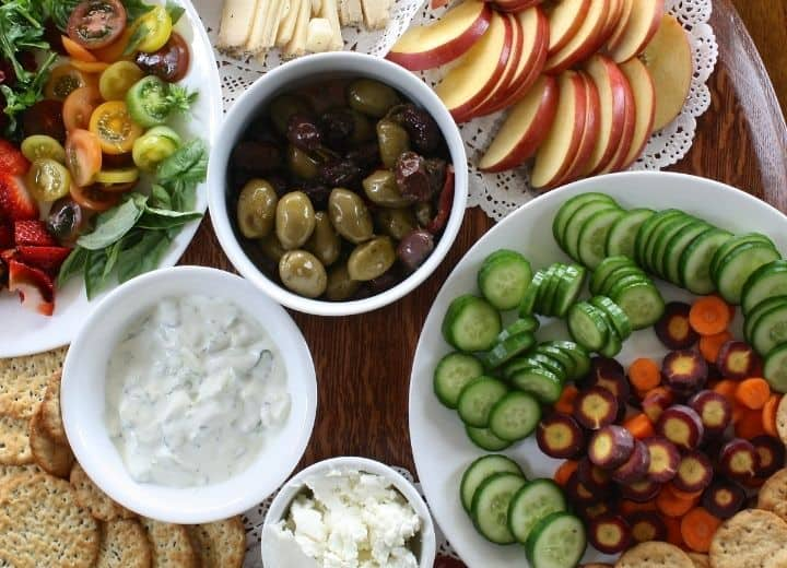 assortment of vegetarian appetizers: sliced fresh veggies, dips, olives, cheese, and apples