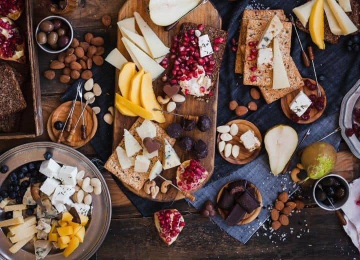 cheeses, crackers, nuts, fruit, and chocolate, on wood platter