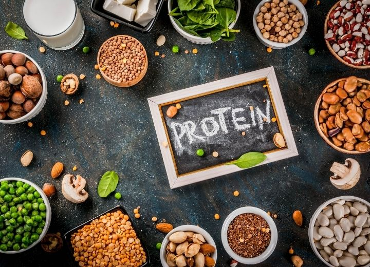 assortment of vegetarian protein sources including lentils, peas, beans in small bowls on black backdrop