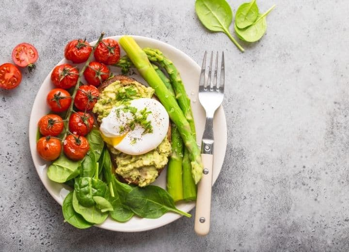 asparagus, tomatoes, spinach, and potato, topped with egg on white bowl - vegetarian gluten free recipes