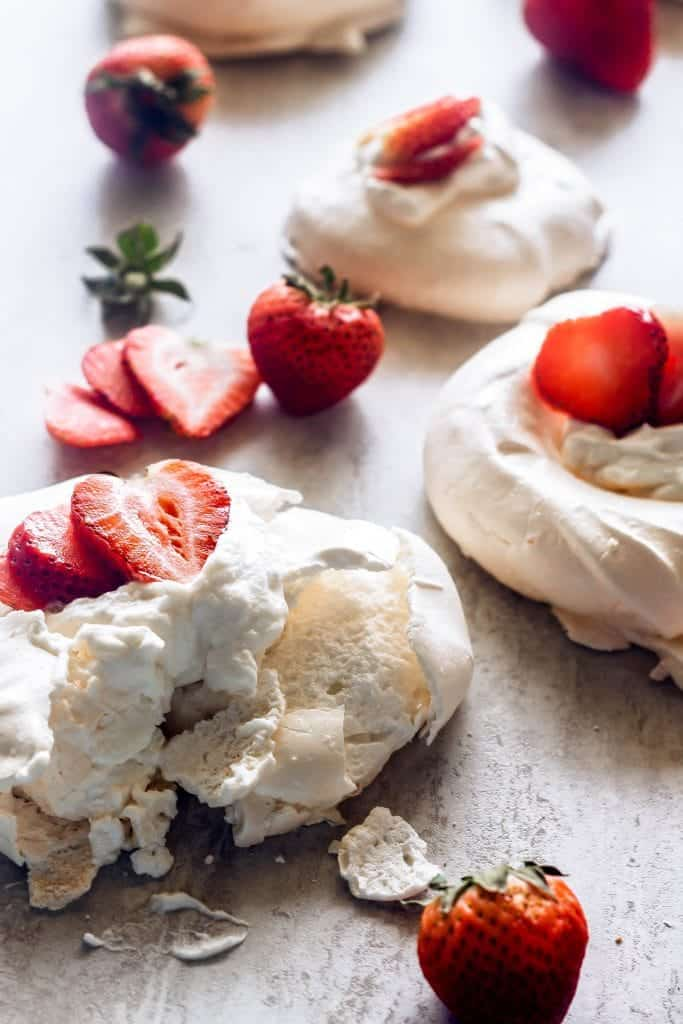 mini pavlovas topped with whipped cream and strawberries