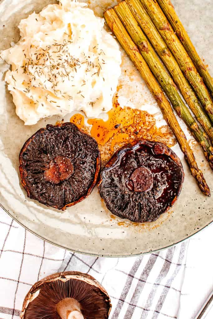 portobello mushroom steaks paired with mashed potatoes and asparagus served on a white plate