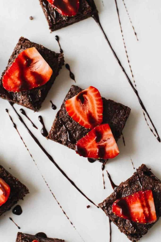brownie squares topped with sliced strawberries and drizzled with chocolate sauce on white plate