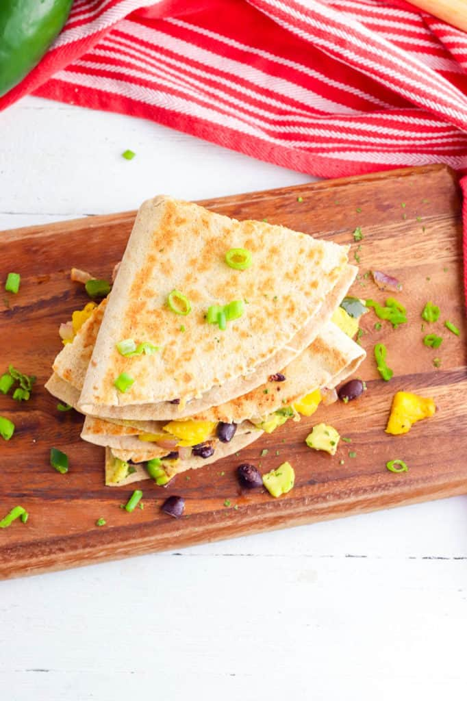 avocado quesadillas with poblanos mangos and black beans stacked on a wooden cutting board