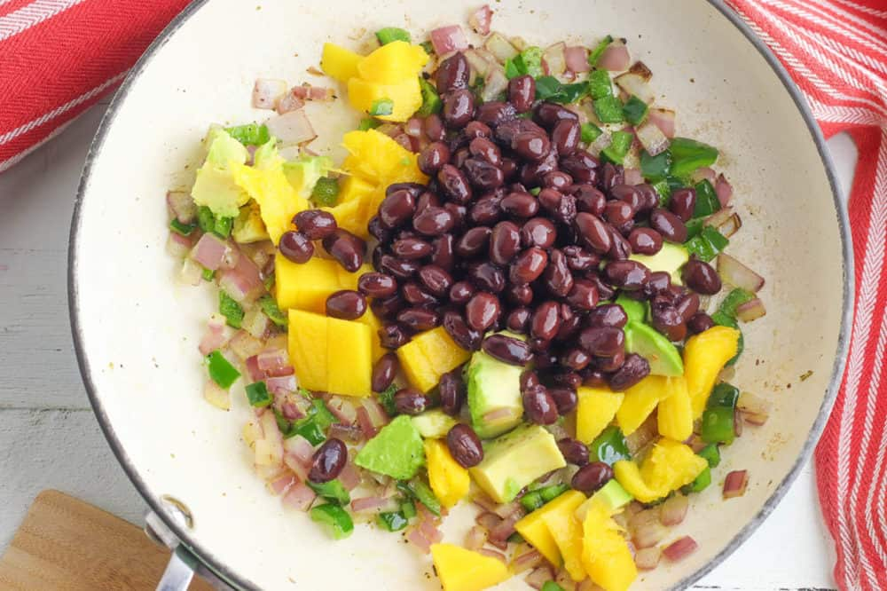 black beans avocados mangos onions and peppers cooking in a pan