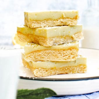 vegan gluten free lemon bars stacked on a white plate