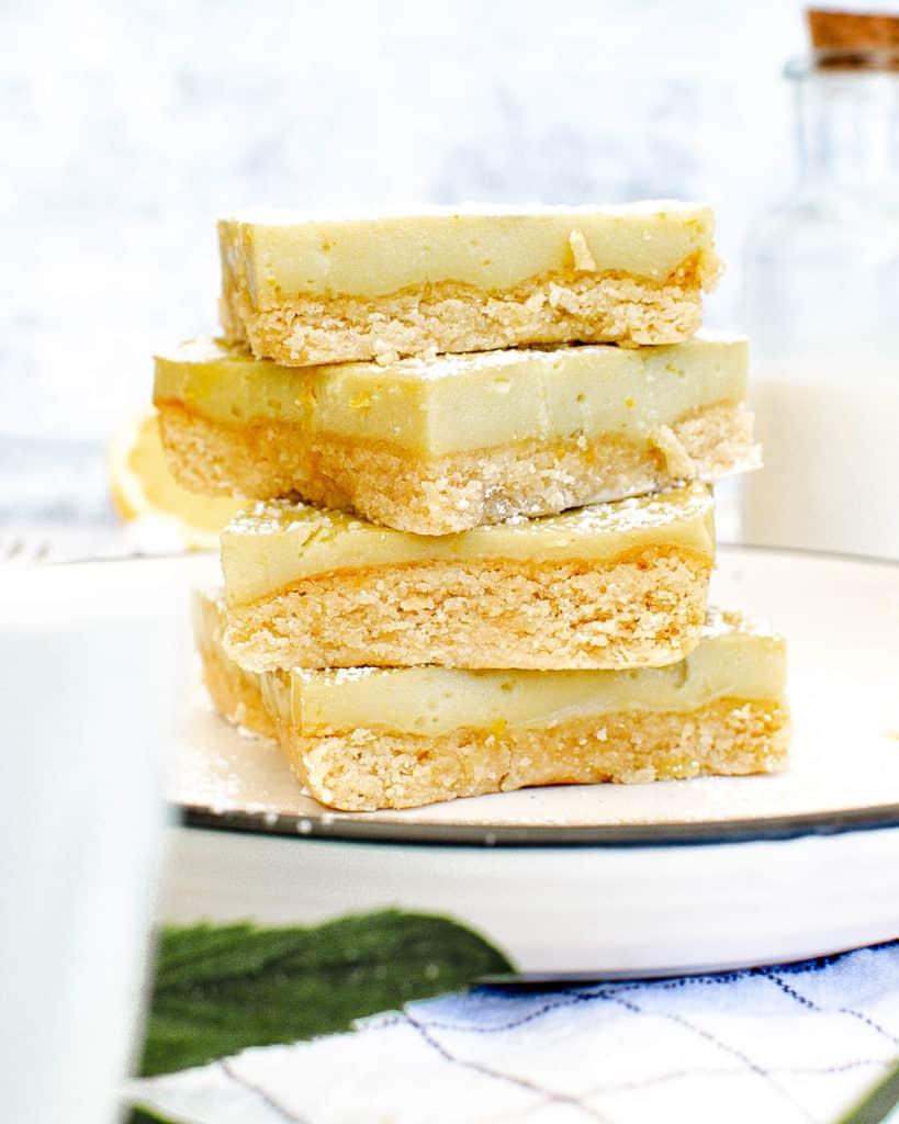 vegan gluten free lemon bars stacked on a white plate