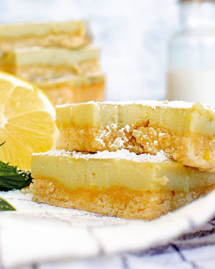 vegan gluten free lemon bars on a white plate with a bite taken out of a bar