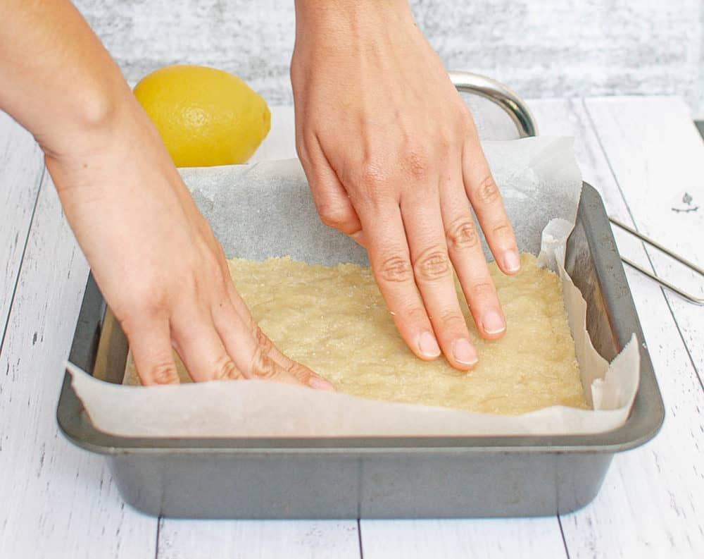 almond crust being pressed into a pan