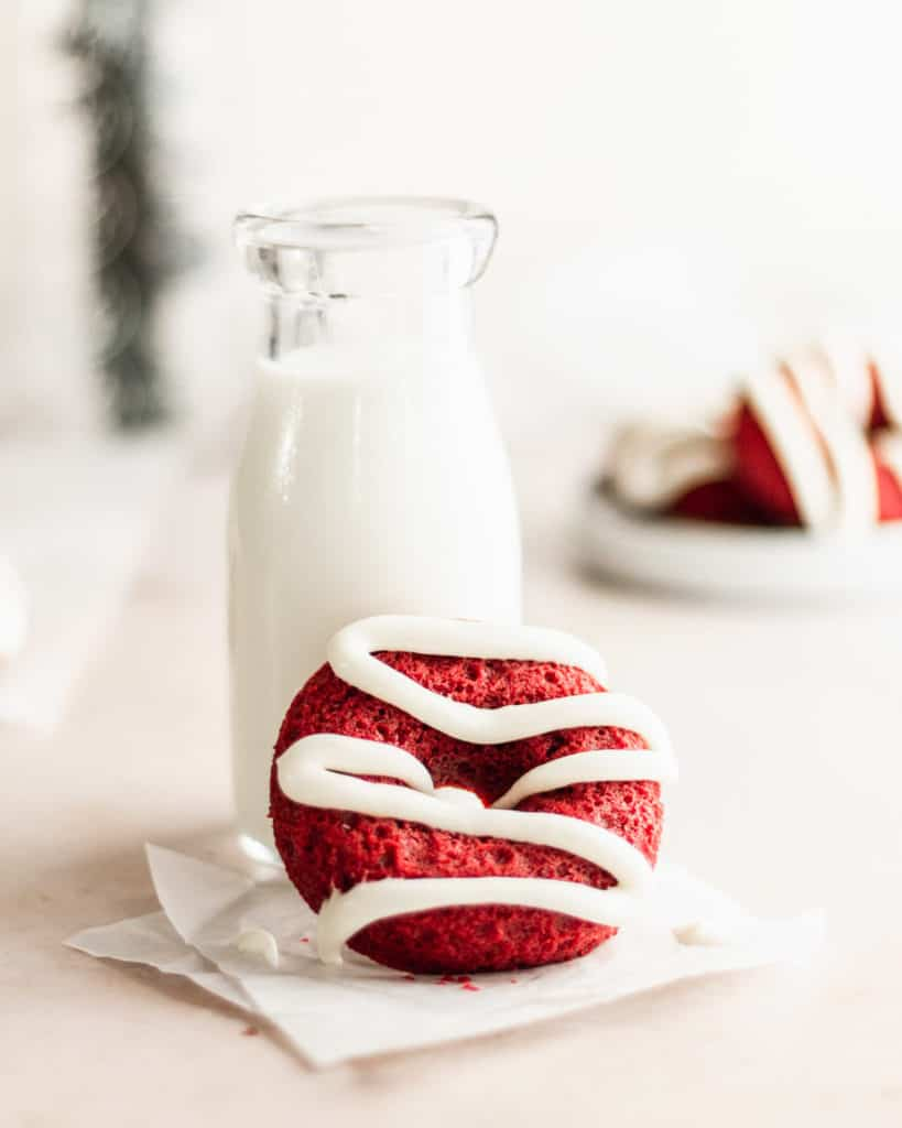 red velvet donut with vanilla icing propped up next to to a small jug of milk