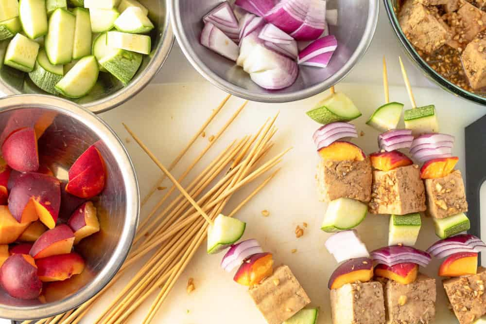 tofu, onion, peaches, and zucchini stuck on kebab sticks