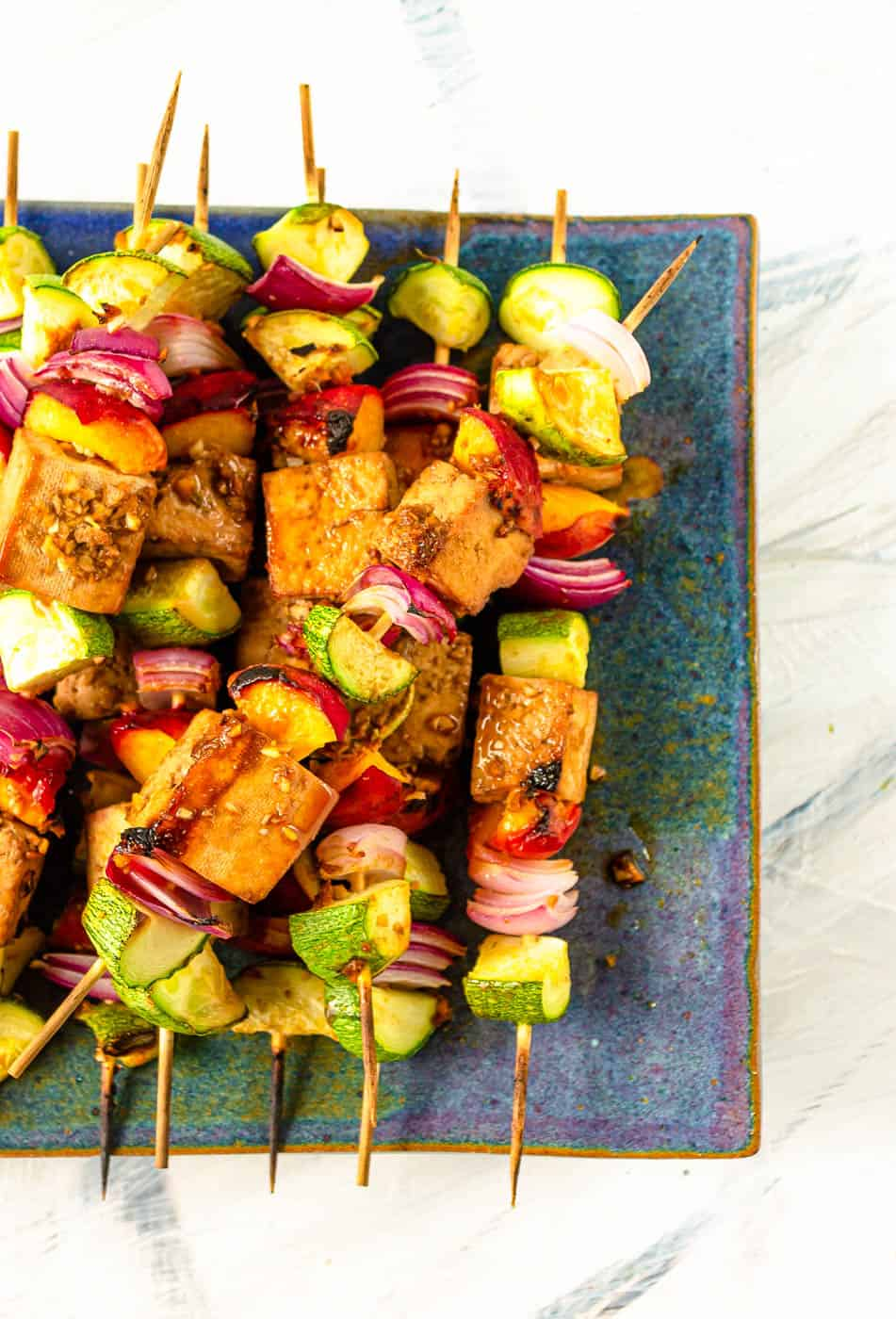 finished tofu skewers on a blue plate