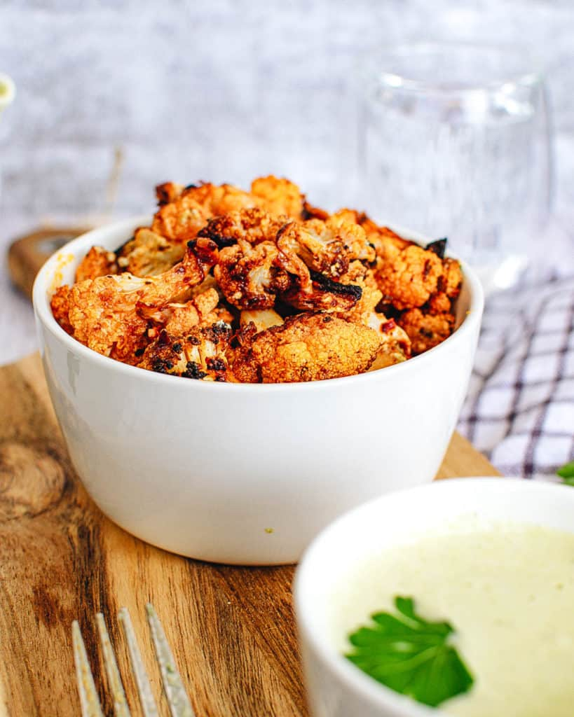 buffalo cauliflower wings with a creamy cashew vegan sauce, served in a white bowl