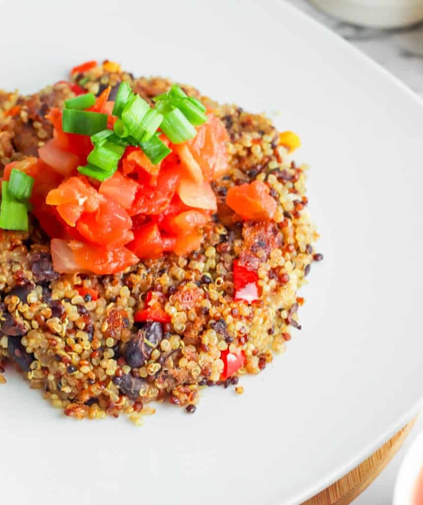 Black Bean Quinoa Cakes topped with salsa, served on a white plate