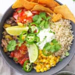 vegetarian burrito bowl with black beans, tortilla chips, corn, cheese and lime