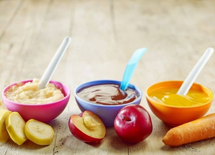 pureed food in small serving bowls including pureed bananas in pink bow, pureed plums in purple bowl, and pureed carrots in orange bowl
