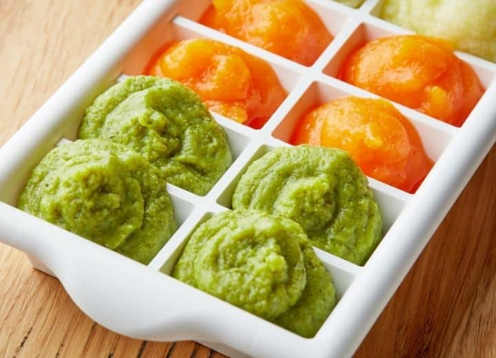 pureed food in ice tray including green peas, orange carrots, and yellow banana puree