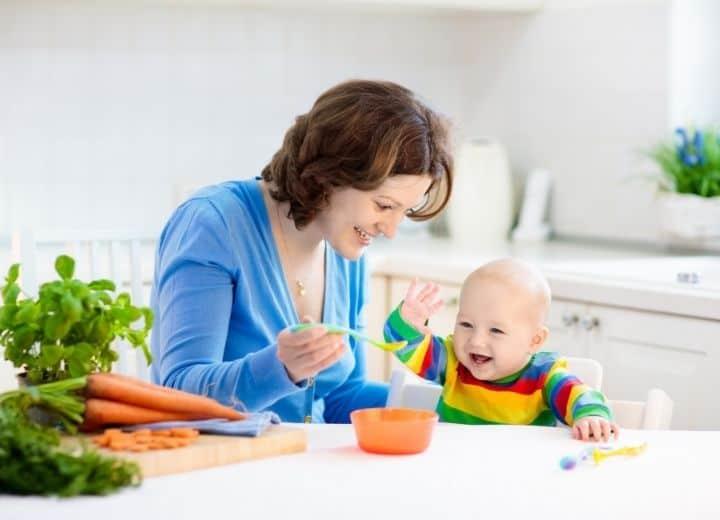 mom feeding happy baby pureed food from orange bowl