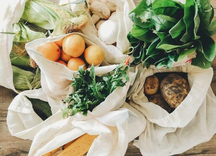 fresh produce in white grocery bags