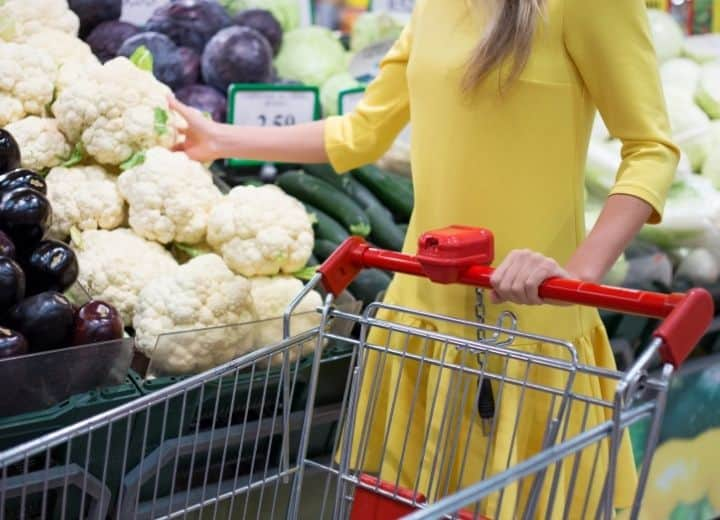 woman pushing grocery cart and picking up a cauliflower