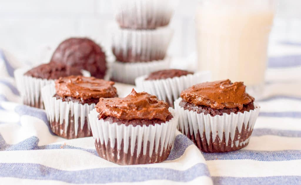 healthy chocolate cupcakes on a blue and white cloth with milk in the background