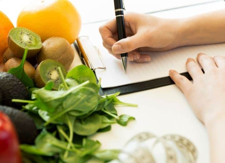woman writing on notepad beside fresh produce - meal planning template