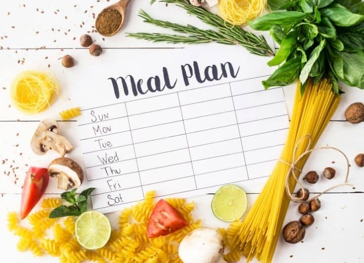 meal planning template surrounded by pasta, basil tomatoes, and mushrooms