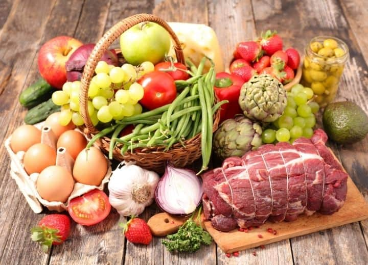 meat, produce, eggs in basket on wood table - organic foods shown for determining is organic food really better