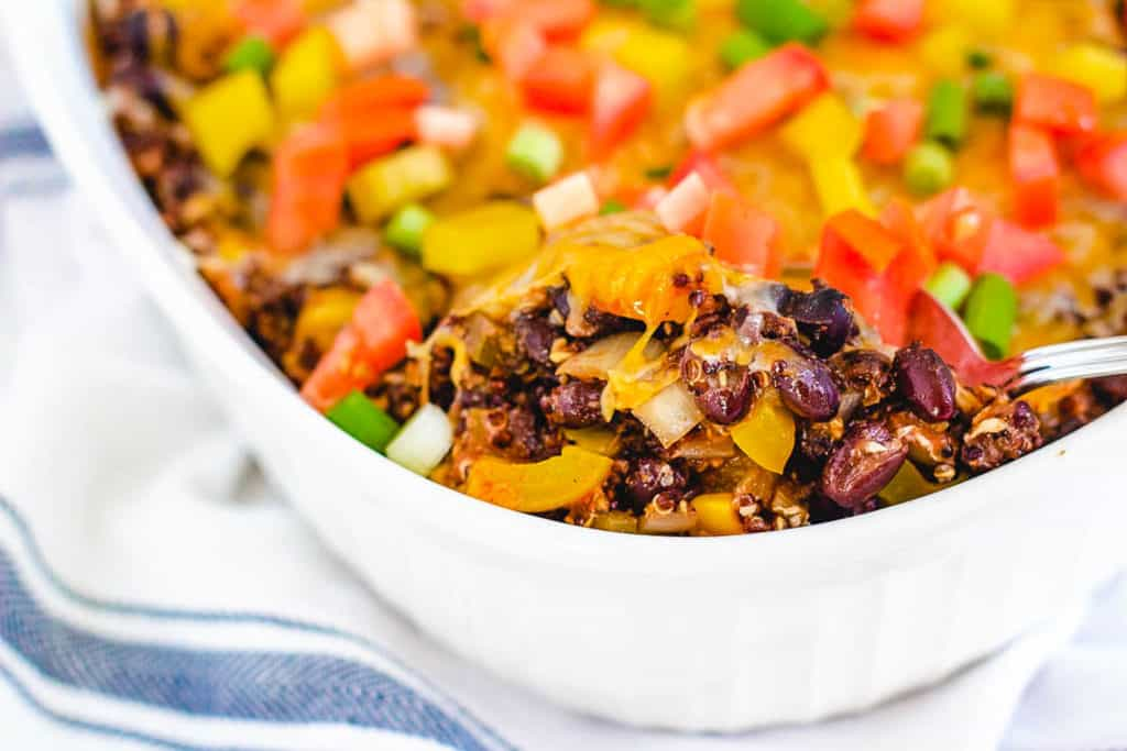black bean casserole with quinoa and cheese, in a white baking dish