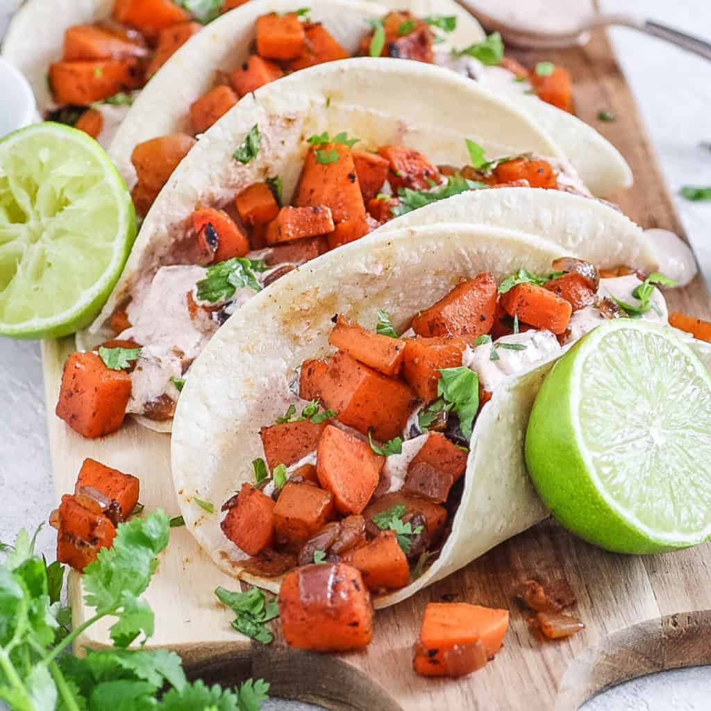 sweet potato tacos with black beans and a spicy yogurt sauce served on a wooden cutting board