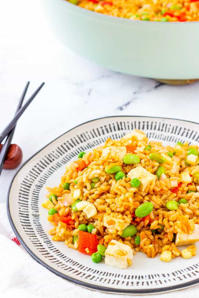 vegan tofu fried rice with vegetables, served on a white plate