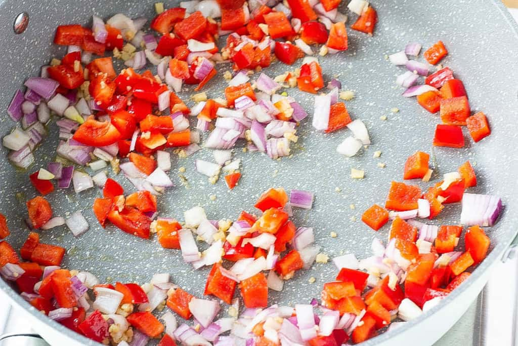 peppers and onions cooking in a pan