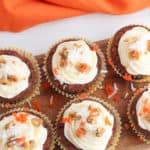 vegan carrot cake cupcakes with vegan cream cheese frosting on wooden cutting board