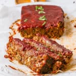 vegan lentil meatloaf / vegan lentil loaf with tomato glaze served on a white plate