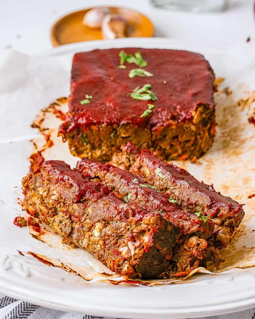 vegan lentil meatloaf / vegan lentil loaf with tomato glaze served on a white plate