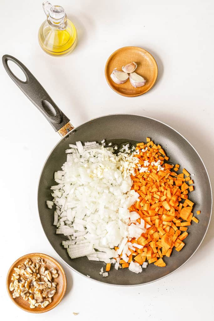 onions and carrots sauteeing in a pan