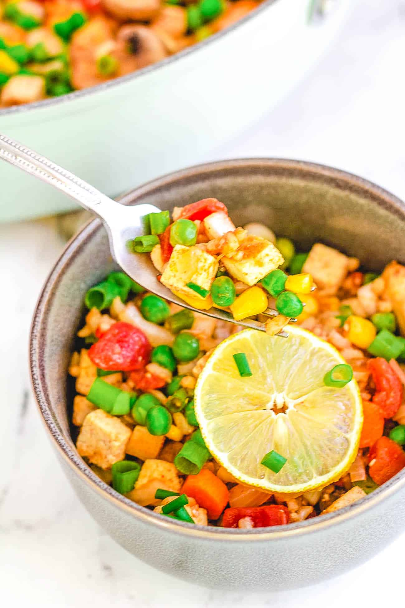 single serving of vegan paella with tofu with a skillet of paella in the background