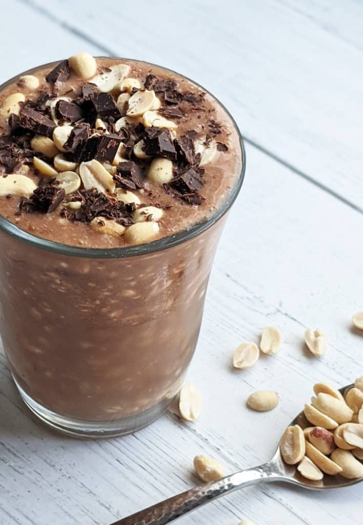 chocolate oatmeal in a cup topped with peanuts and chocolate shavings