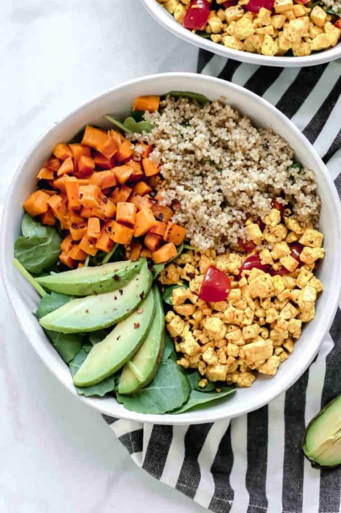 veggie breakfast bowl with scrambled tofu, quinoa, sweet potatoes, and sliced avocado