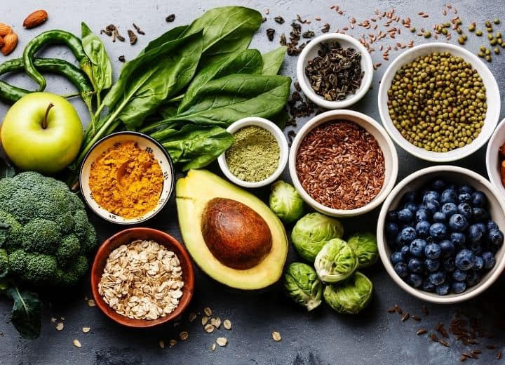 assorted healthy foods in small bowls: broccoli, apple, basil, hot pepper, avocado, brussel sprouts, flax seeds, blueberries - all ingredients on a vegetarian grocery list