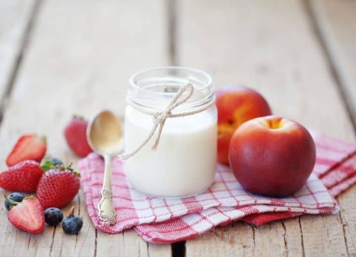 milk in jar, surrounded by strawberries, blueberries and nectarines - natural sugar vs. added sugar