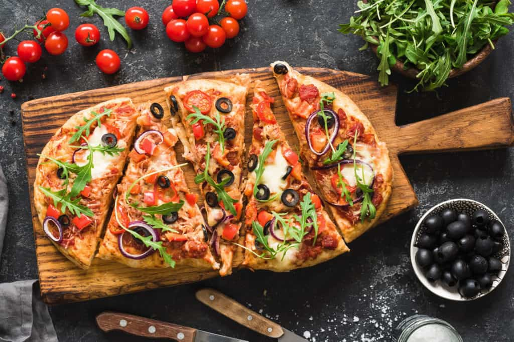 Flatbread pizza garnished with fresh arugula on wooden pizza board, top view. Dark stone background - healthy pizza toppings
