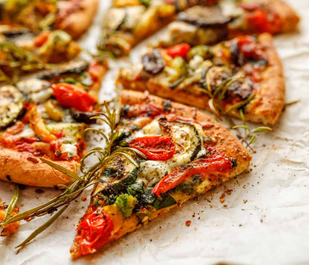 Vegetarian pizza with addition grilled vegetables and aromatic herbs, divided into portions