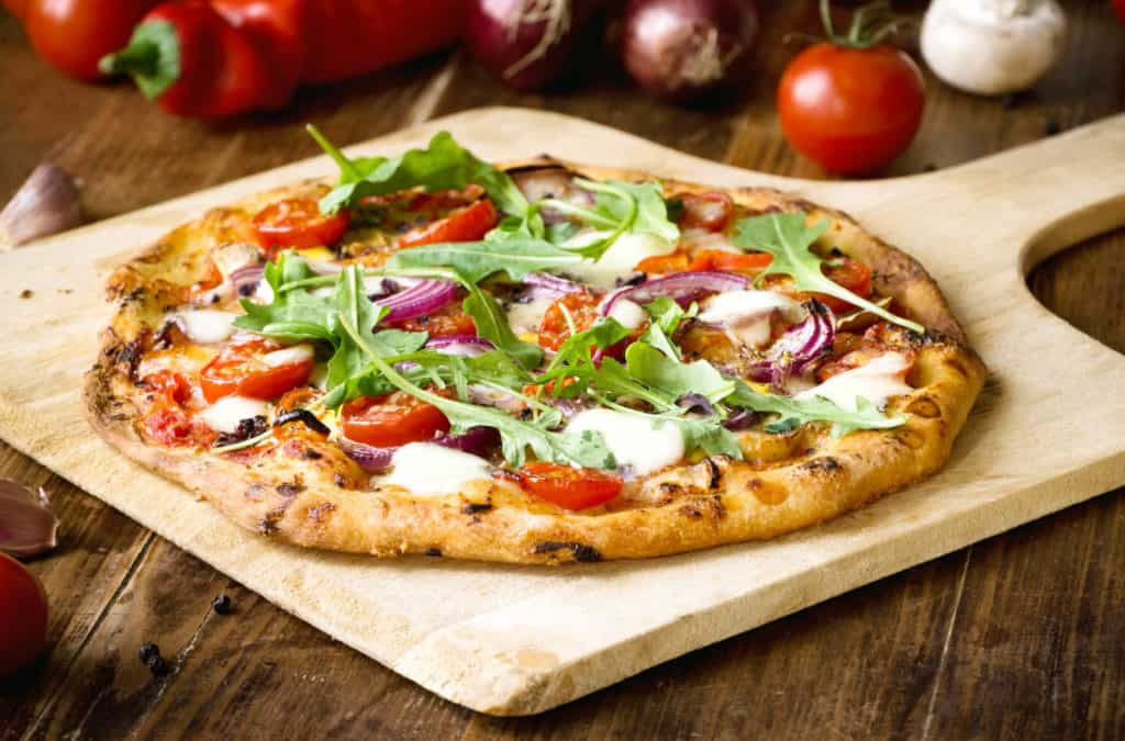 Freshly baked pizza with arugula, tomato, red onion and mozzarella - healthy pizza toppings