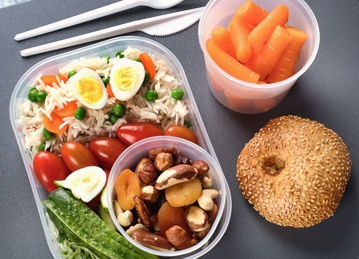healthy plane snacks: cup of carrots, whole wheat roll, rice and vegetables, hard boiled egg, and cup of nuts